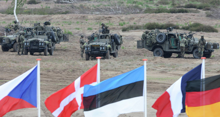 Flags wave in front of soldiers who take positions with their army vehicles during the NATO Noble Jump exercise on a training range near Swietoszow Zagan, Poland, Thursday, June 18, 2015.